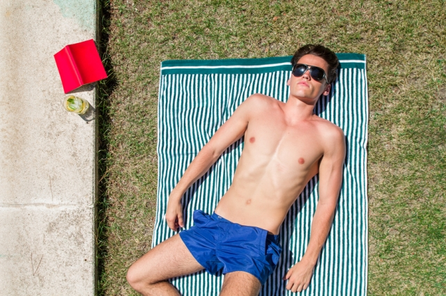 Young Man Sunbathing Lying On A Towel In A Garden Near A Pool
